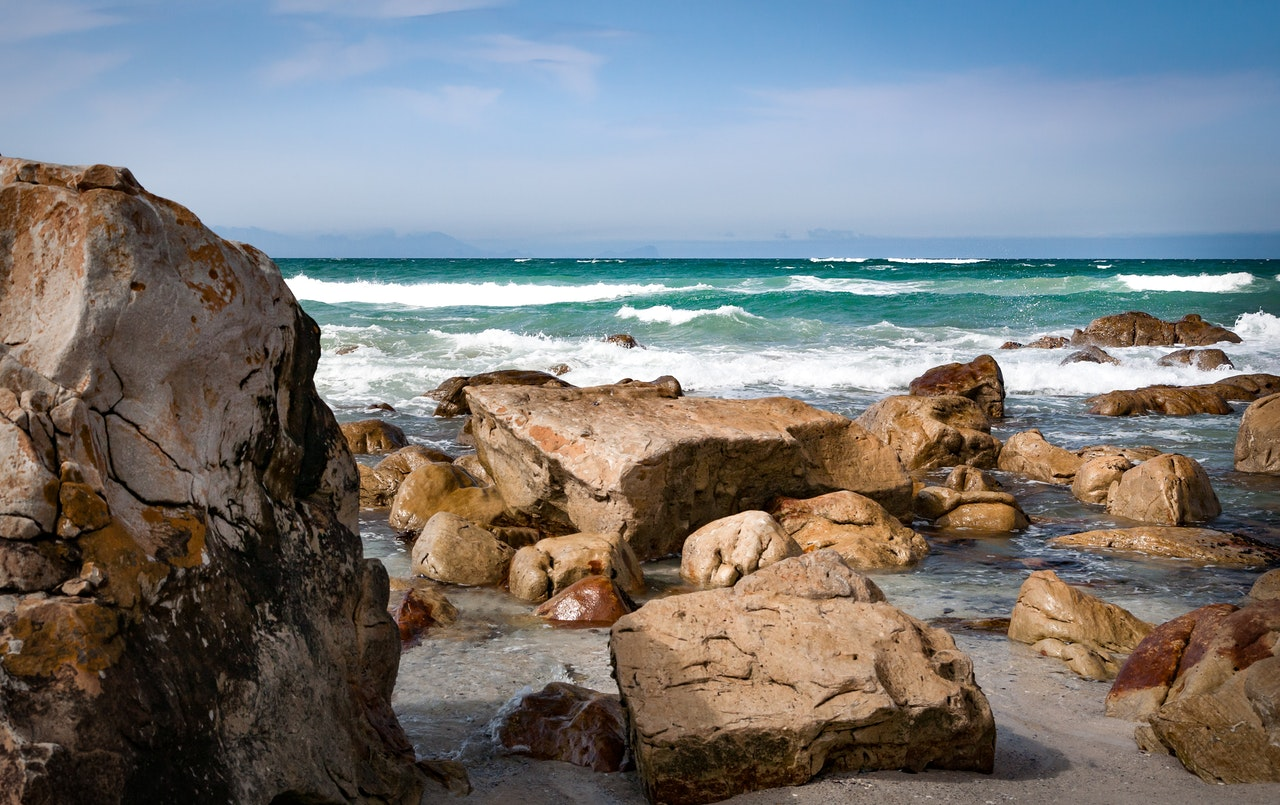 seashore with rocks under blue sky